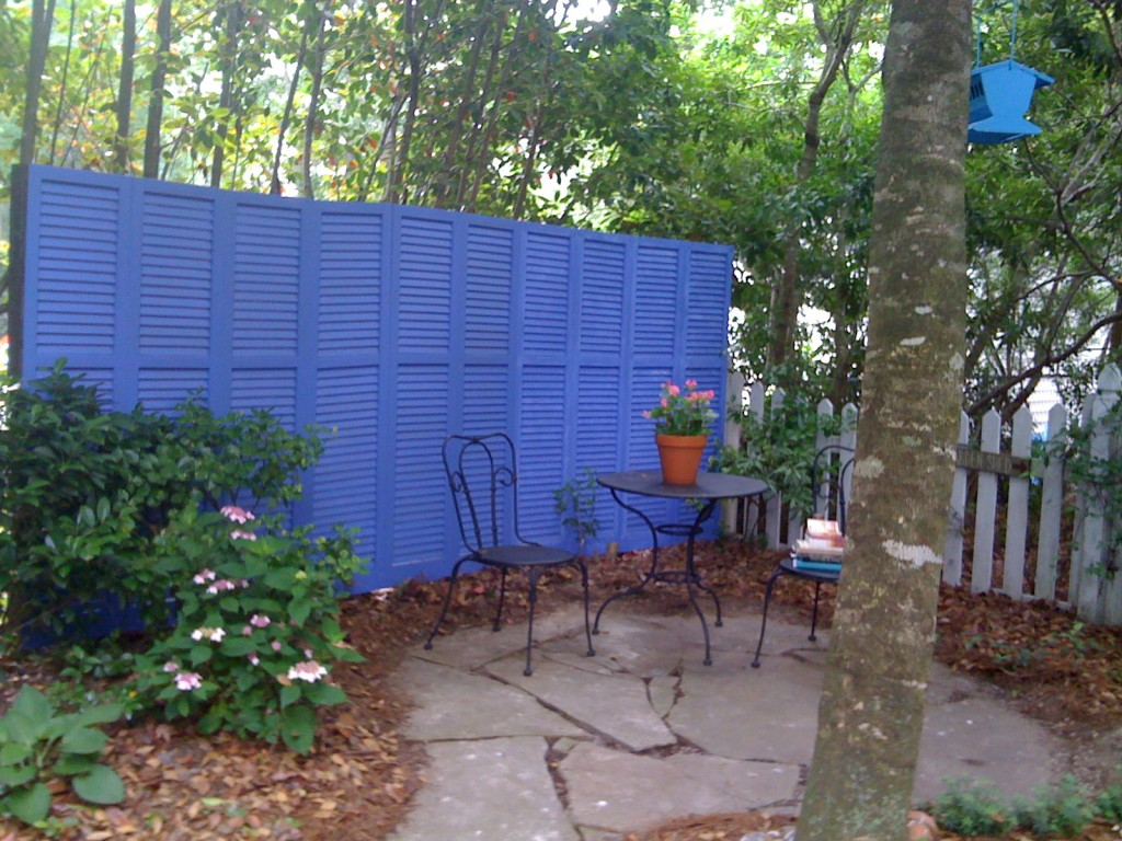 Use a stack of old shutters to add more privacy to your outdoor oasis